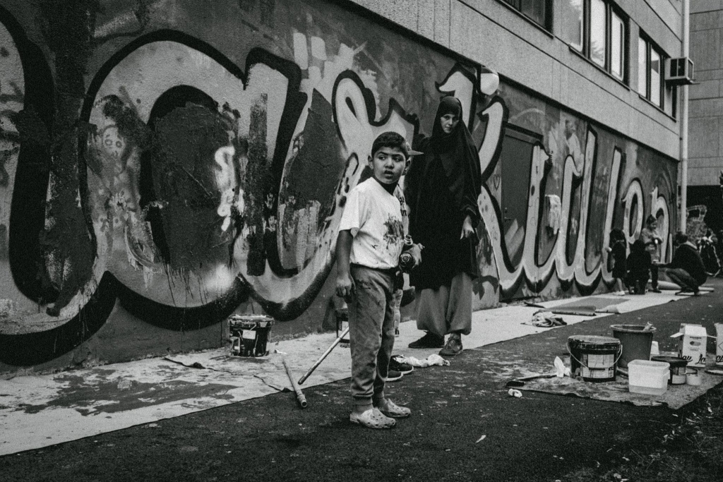 Photo of a kid who has been painting a wall, and his mother by futuro berg