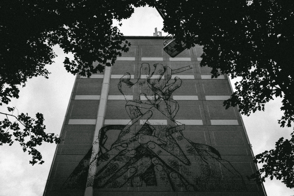 Photo of a stencil art mural with hands scratching the facade of 9 story building by futuro berg