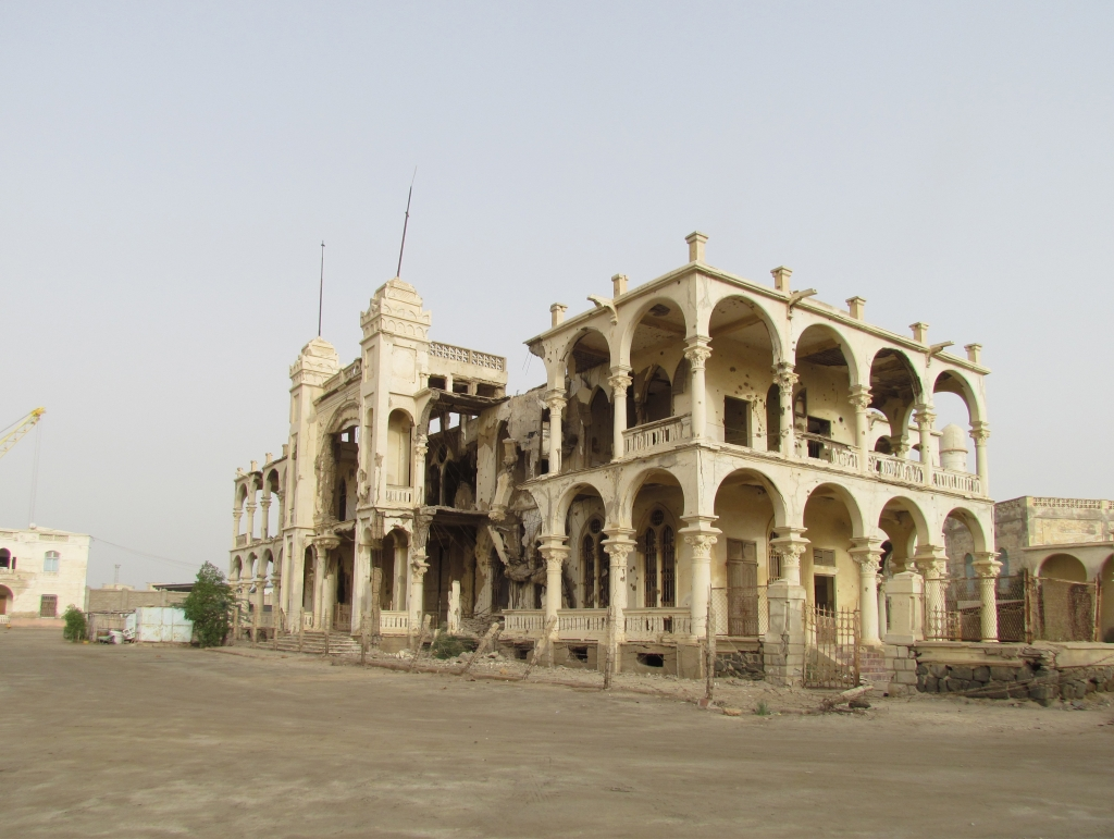 Ruin of the Bank of Italy building, Massawa, completed in the 1920s and heavily damaged during the war between Ethiopia and Eritrea. The cranes show that the harbour is in use despite all ruined buildings around. Photo: Soroor Notash. February 2019